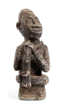 A STONE SEATED FIGURE