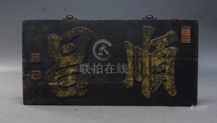 A Chinese calligraphic panel, 19th century, carved in relief with two characters, with seals to left