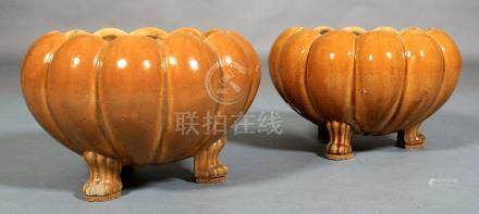 A PAIR OF CHINESE MUSTARD GLAZED JARDINIERES, of pumpkin shape, each on three paw feet,