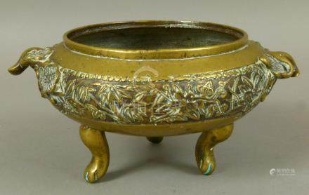 A CHINESE BRONZE TWO HANDLED CENSER of compressed cauldron form,
