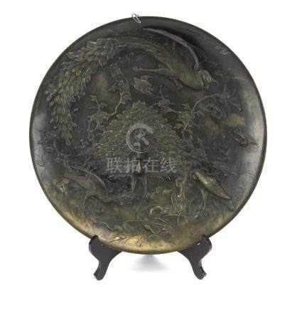 A brown patinated bronze charger of circular form relief decorated with peacocks and other birds,