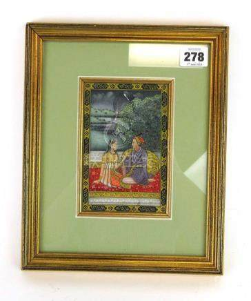 An Indian miniature painting on marble depicting a couple seated in a garden, 14 x 9.