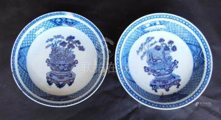 Pair of Chinese Kang Xi blue and white dishes decorated with a flower-filled vase to the centre, one
