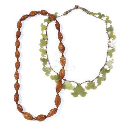 Soapstone panel necklace Chinese, circa 1900/1920, together with a peach stone/ nut bead necklace,