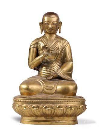 LAMA ASSIS sur une base à décor de lotus, en cuivre repoussé doré, les mains en