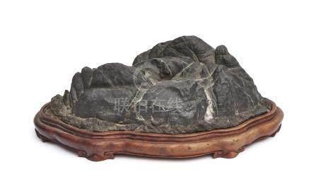 Pierre paysage suiseki gris-noir en forme de paysage de montagne, sur un platea