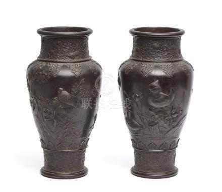 Ensemble de deux grands vases en bronze, décorés en relief d'oiseaux, fleurs de