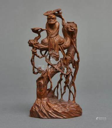 Sculpture en buis représentant le patriarche zen Daruma assis sur une branche d