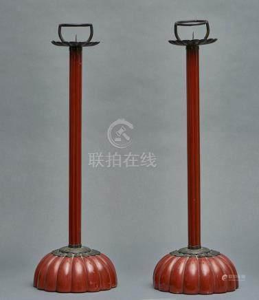 Ensemble de deux bougeoirs en bois laqué brun rouge foncé avec un pied en forme