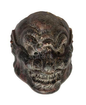 Masque en bois de couleur noire, représentant le visage grimaçant d'un vieil ho