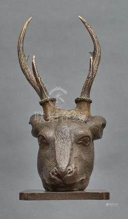 Tête de cerf en bois gravé, placée sur un socle en bois, et munie de vrais bois