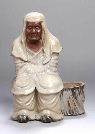 Keramik-Figur, Japan, Meiji-Periode, auf ausgehöhltem Baumstumpf vollplastische, sitzendePerson,