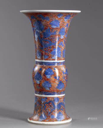 A Chinese iron-red-ground blue and white 'dragon and lotus' vase, gu