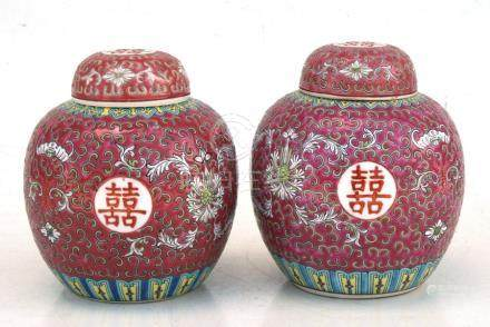 A pair of Chinese famille rose ginger jar and covers, decorated foliate scrolls on a pink ground.