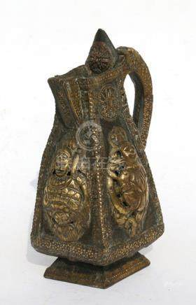 A Tibetan wooden jug with brass mounts depicting deities, 26cms (10.25ins) high.