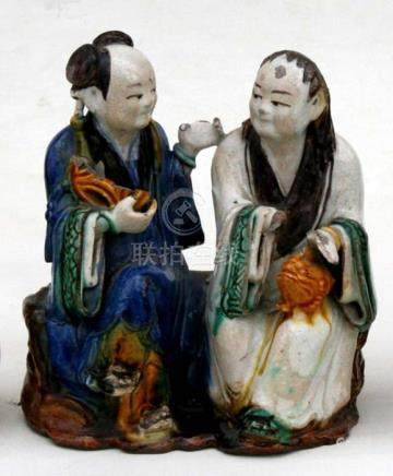 A Chinese Sancai glazed group depicting two seated robed figures, 19cm (7.5ins) high.