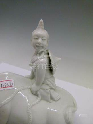 Chinese blanc de chine figure, depicting a boy seated on a buffalo, 14cm high Condition: **General