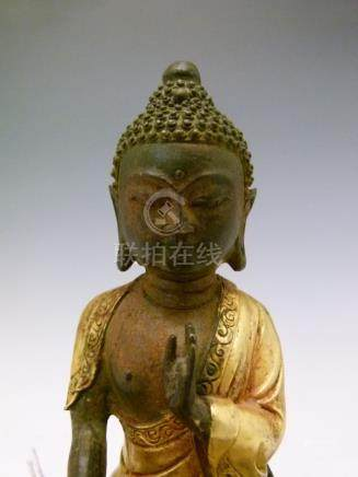Partially gilded bronze figure of a seated Buddha, probably Sino-Tibetan, his left hand raised,