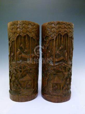 Pair of Chinese carved bamboo brush pots, each decorated with figures in a woodland setting, 26.25cm