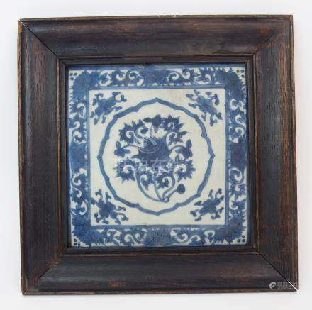 A CHINESE BLUE AND WHITE TILE painted with a central lotus roundel surrounded by foliate spandrels