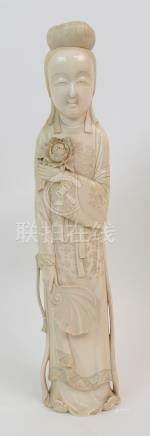 A JAPANESE MEIJI IVORY OKIMONO of a lady holding a peony in one hand and a fan in the other, her