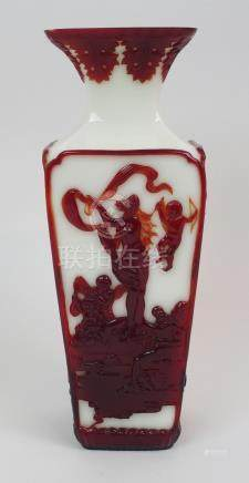 A PEKING OVERLAID GLASS VASE of square tapering form carved in red with mythological scenes on a