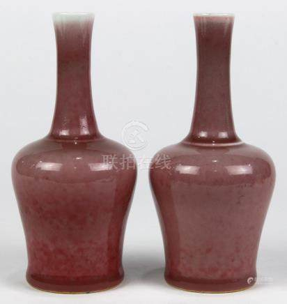 Pair of Chinese oxblood glazed small vases, of mallet form with a long neck and wide shoulders above