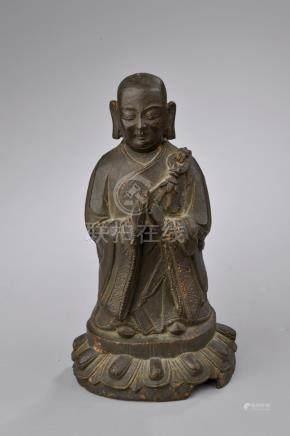 CHINE - Époque MING (1368 - 1644).Statuette de moine debout en bronze à patine