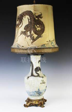 A Chinese crackle glaze lamp, moulded with a dragon and a carp, with an embroidered shade,