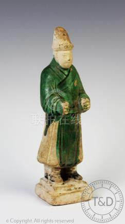 A Chinese funerary figure, Tang Dynasty, earthenware body, glazed in green,