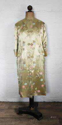 A Chinese silk day robe, worked with flowers against a golden coloured ground,