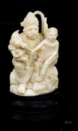 An early 20th century Indian ivory group depicting a seated figure with a child and Ganesh on his