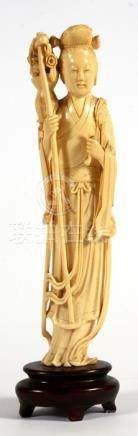 A late 19th / early 20th century Chinese figure depicting a robed maiden holding a staff and a