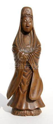 A Chinese carved wooden figure depicting Guanyin, 20cms (8ins) high.