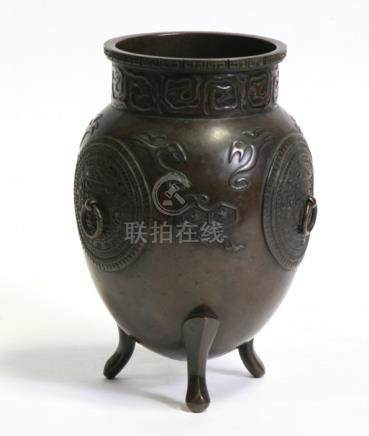 An Oriental bronze vase with three ring handles, on tripod legs, 21cms (8.25ins) high.