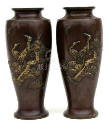 A pair of Japanese bronze vases decorated in relief with cranes. 23cm (9 ins) high