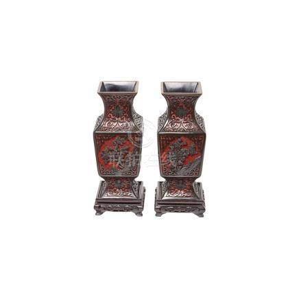 Pareja de jarrones chinos en laca roja tallada con decoración floral en relieve sobre peana en