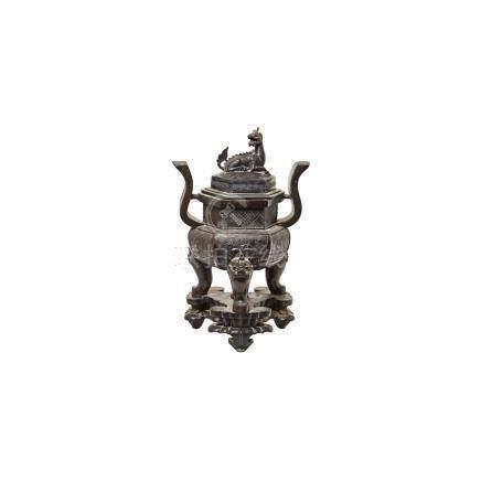 Gran incensario chino, dinastía Qing, en bronce patinado con decoración geométrica, de mascarones
