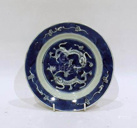 Chinese Kangxi porcelain small dish, circular and decorated with pair of kylin on a blue wash