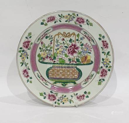 Chinese porcelain plate painted in famille rose colours with a basket of flowers, 23cm dia.