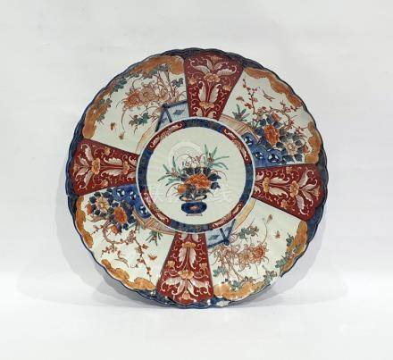 Large Japanese Imari porcelain charger, circular and with scalloped border, floral vase to centre