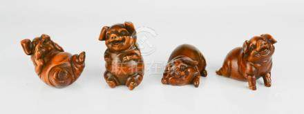 Four Chinese hand carved boxwood figures of 'happy pigs'.