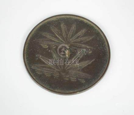 An Eastern Han Dynasty Chinese bronze mirror, 1-2nd century AD, depicting lotus leaves.