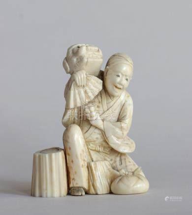 OKIMONO en ivoire représentant un homme accroupi tenant un éventail et un cloch