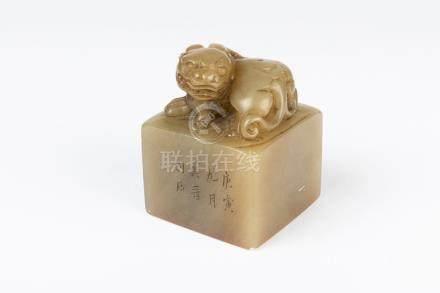 CHINE. CACHET en pierre dure sculpté et gravé, la base surmontée d'un chien de