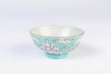 CHINE. Petit BOL en porcelaine à décor polychrome de rinceaux sur fond bleu cie