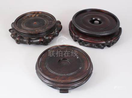 THREE 19TH CENTURY CHINESE CARVED WOOD VASE STANDS. 20cms, 16cms and 15cms diameter.