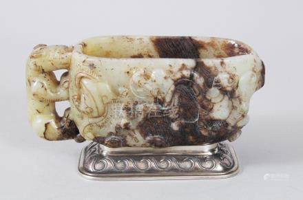A CHINESE 18TH CENTURY CARVED JADE LIBATION CUP, the sides carved with animals and scrolls, on a