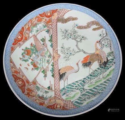A Japanese Kakiemon charger Meiji period Delicately decorated with a scene of cranes by a