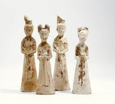 Four Chinese unglazed pottery figures of ladies, each simply dressed in a long robe and shawl,